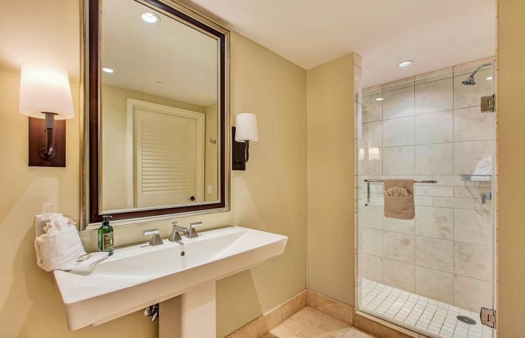 Luxurious guest bathroom with glass and travertine walk-in shower