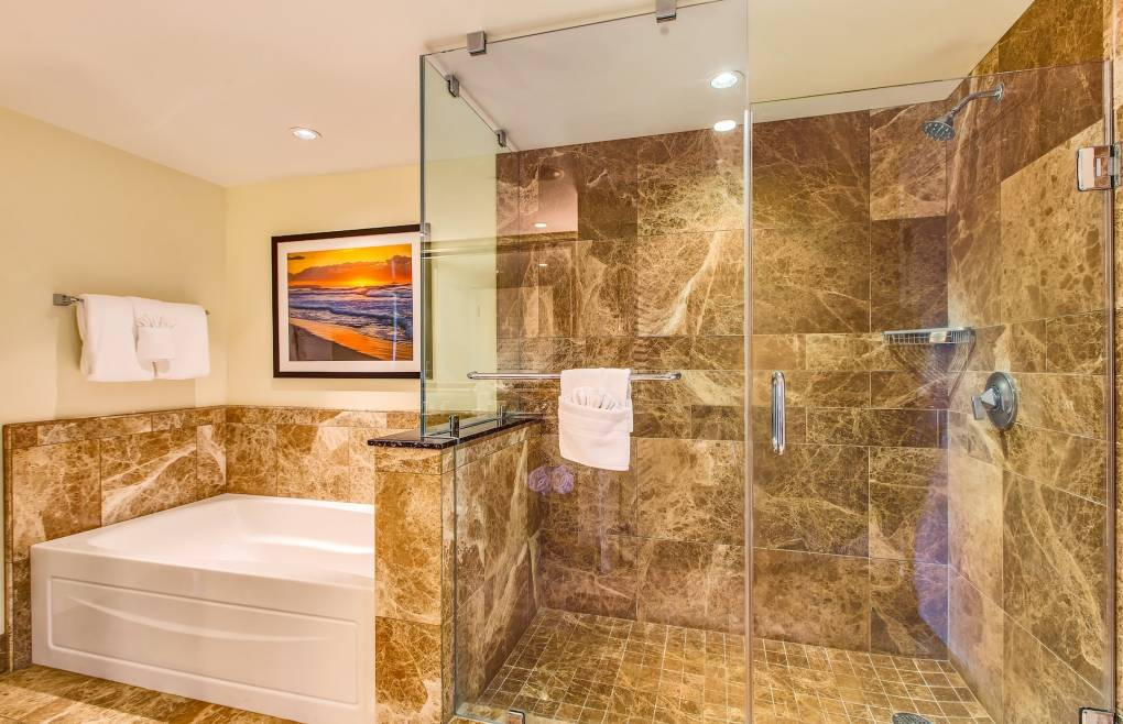 With a glass and marble walk-in shower and a separate soaking tub
