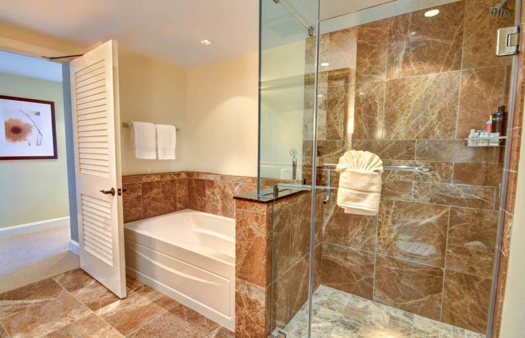 With a glass and marble walk-in shower and separate soaking tub