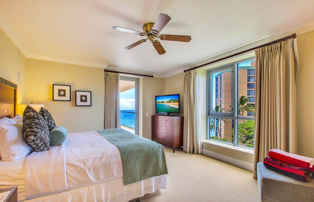 The spacious master bedroom features a king-size bed and balcony access