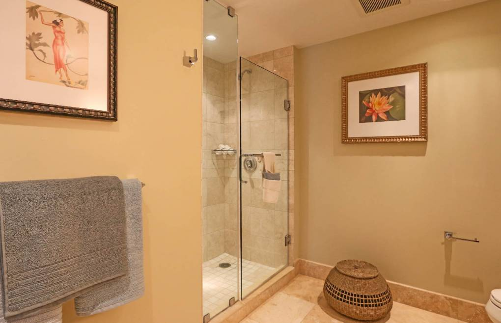 Featuring a glass and travertine walk-in shower