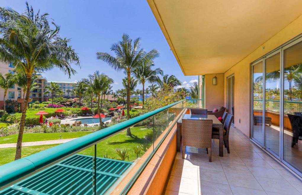 The large balcony offers partial ocean and lush courtyard views