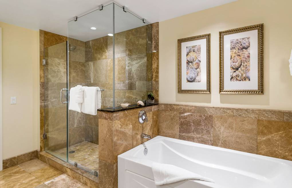 With a glass and marble shower and separate soaking tub