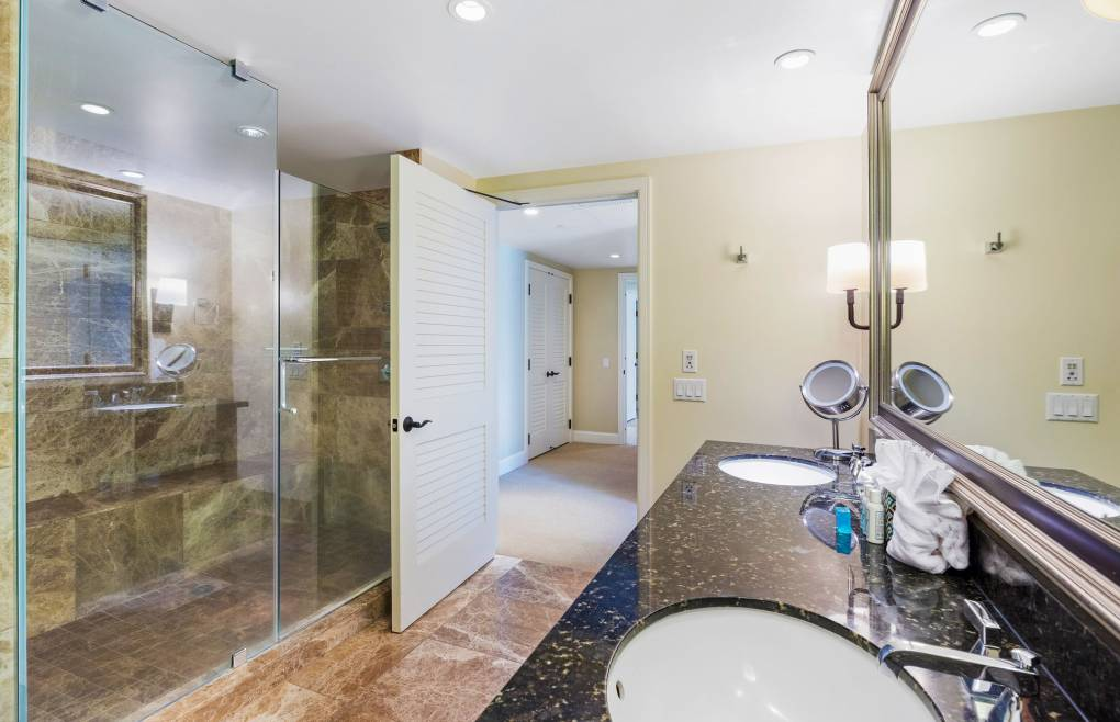With a glass and marble walk-in shower and a double granite vanity