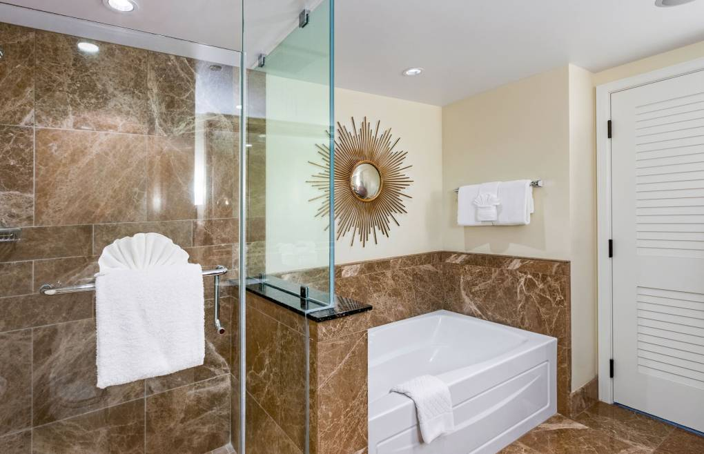 With a frameless glass walk-in shower and a separate soaking tub