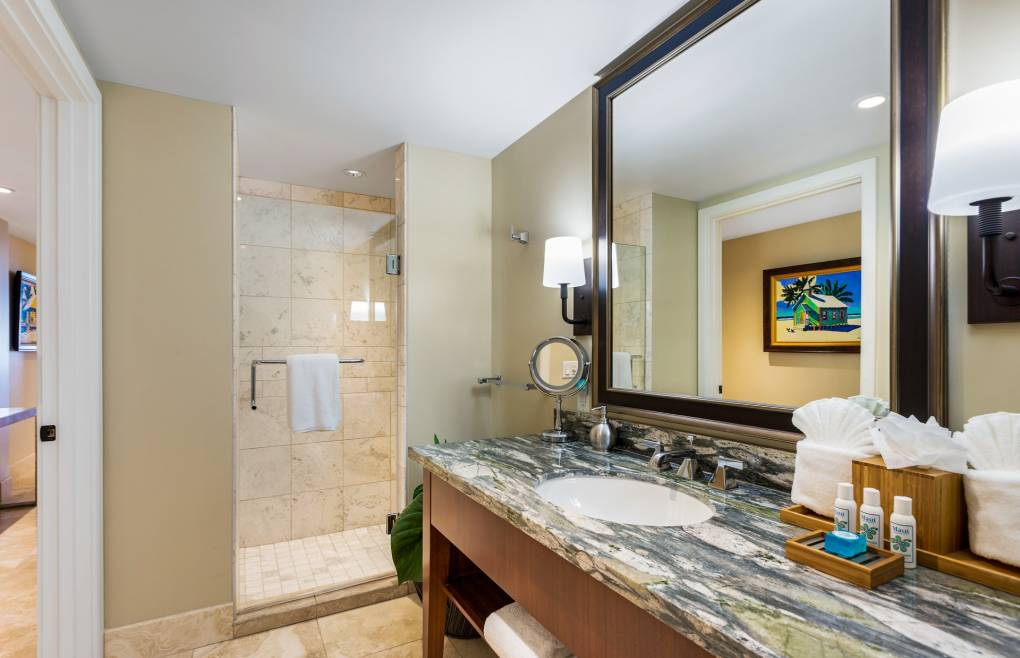 The guest bathroom offers a granite vanity with a glass and travertine walk-in shower