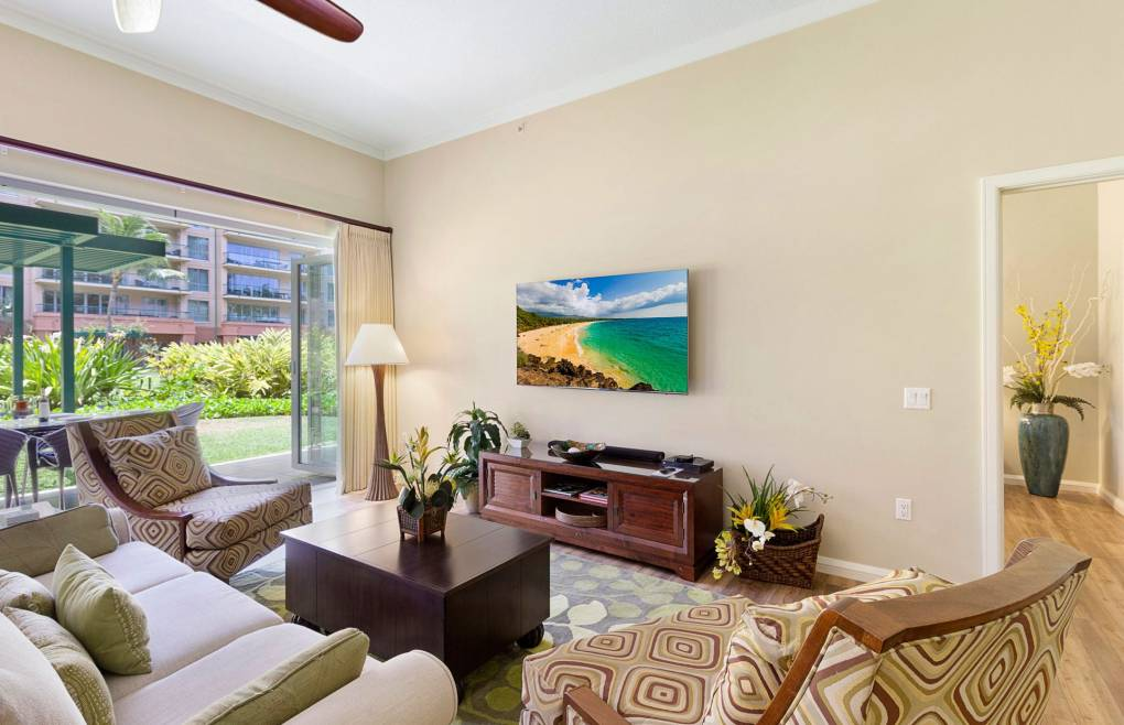 """The living room features a 65"""" wall-mounted smart TV"""