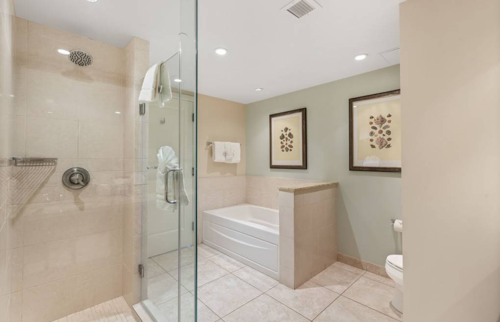 The guest bath also offers a glass walk-in shower and separate soaking tub