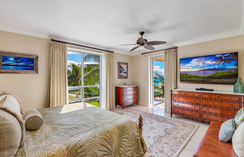 The spacious master bedroom features a king-size bed, ocean views, and balcony access